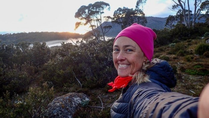 female hiker with pink beanie smiles to camera with misty scene behind