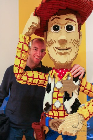 Aaron posing with a giant Lego Woody from Toy Story in the Magnificent Mile in Chicago | LotsaSmiles Photography