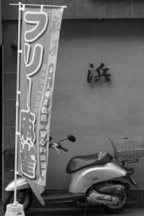 A moped hides behind a mah-jong banner outside a modest building in Mitaka, Tokyo, Japan.