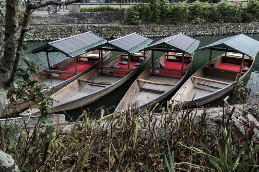 Hozu River boats await their daily tourists coming to explore the lazy river in Arashiyama.