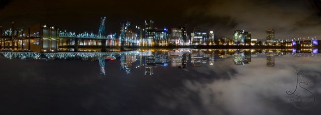 The Willamette River perfectly reflects the night skyline of Portland