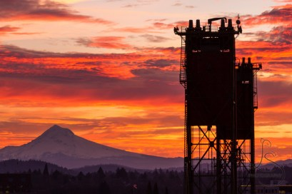 A Portland sunrise silhouettes Mount Hood and the tops of the Hawthorne Bridge towers