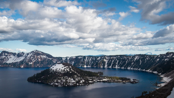 Snow-capped Wizard Island in Crater Lake on a partly cloudy day | LotsaSmiles Photography