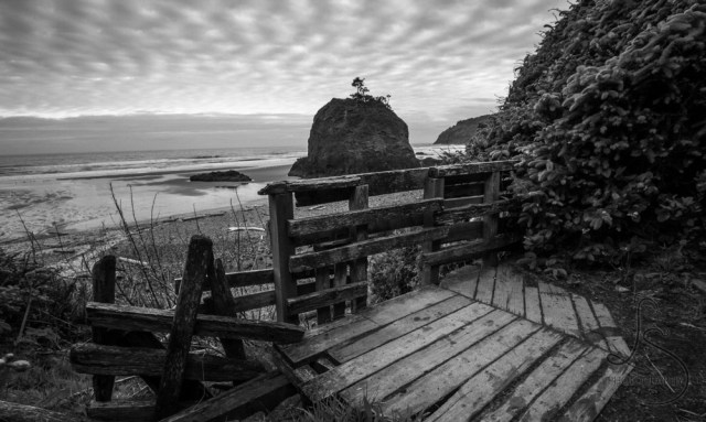 A small beach cove, dominated by a large boulder, under fish-scale clouds   LotsaSmiles Photography