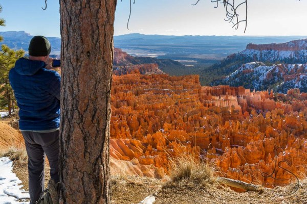 A fellow photographer braces himself against a tree for a steady shot of the Bryce Canyon landscape | LotsaSmiles Photography