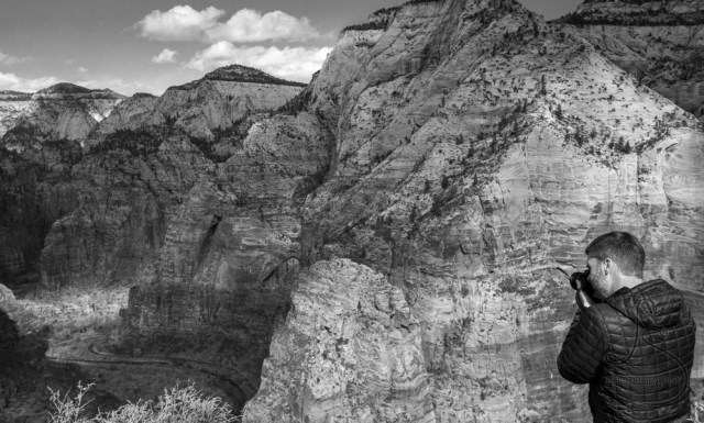 Black and white image of a man photographing the Zion valley | LotsaSmiles Photography
