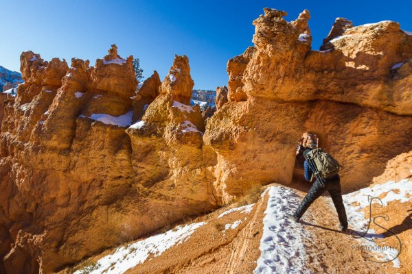 One of our fellow hikers bending to get just the right angle on a tunnel in Bryce Canyon | LotsaSmiles Photography