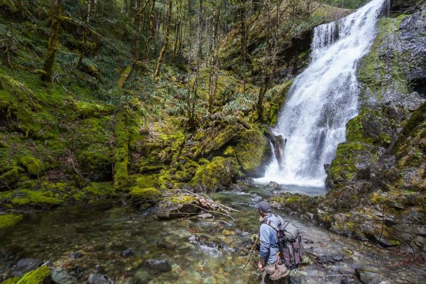 Hiker wading out into a waterfall's pool | LotsaSmiles Photography