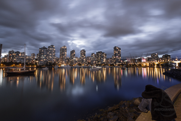 Vancouver skyline at dusk under a cloudy sky with a person crouched in the foreground | LotsaSmiles Photography