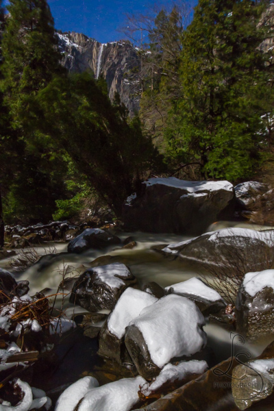 Nighttime moonscape of Yosemite Falls with snowy rocks in a frozen creek in the foreground | LotsaSmiles Photography