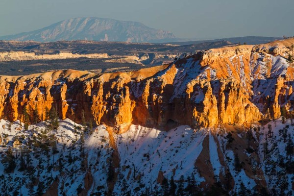 Hoodoos illuminated by sunset, with a distant plateau on the horizon in Bryce Canyon | LotsaSmiles Photography