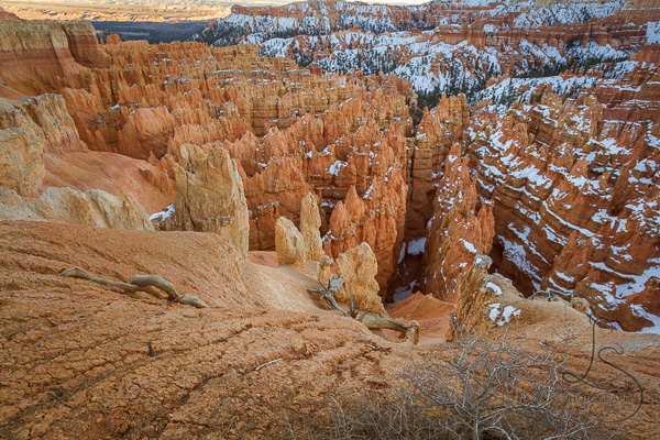 The edge of the canyon, looking down at snowy hoodoos at sunset in Bryce Canyon | LotsaSmiles Photography