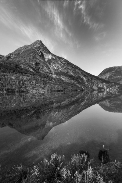A Norwegian hill reflected in a perfectly still fjord, in monochrome | LotsaSmiles Photography