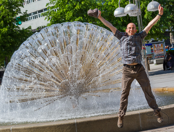 Aaron jumping in front of a fountain in Oslo, Norway | LotsaSmiles Photography