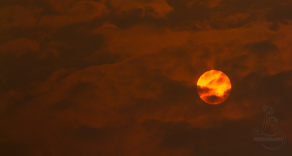 A fire-orange sun peeking through the clouds in a blood-red sky | LotsaSmiles Photography