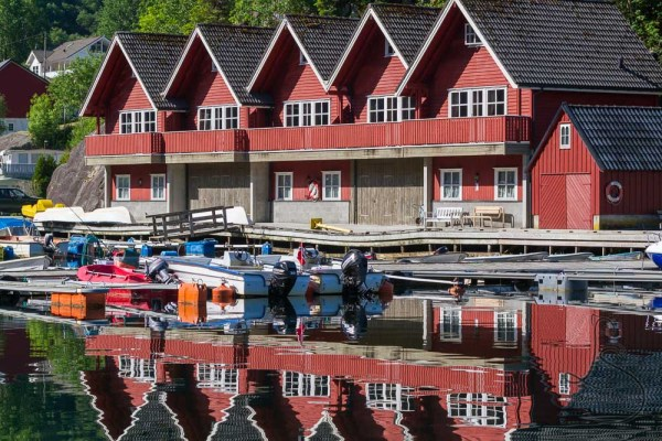 Red cabins beautifully reflected in the cove waters at Kyrping in Norway | LotsaSmiles Photography