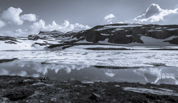 Snowy lake reflecting the frozen landscape in Norway, in monochrome | LotsaSmiles Photography