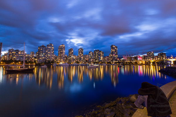 A person crouched on the waterfront as evening descends on the illuminated city of Vancouver | LotsaSmiles Photography