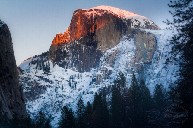 The sun sets in Yosemite National park, slipping off of the tip of Half Dome   LotsaSmiles Photography