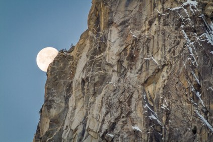 The moon sets behind a Yosemite cliff face.