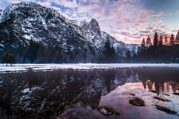 A snowy hill reflected in a still lake in Yosemite National Park at dusk | LotsaSmiles Photography