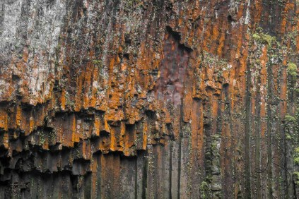 A rust-colored basalt wall stands behind a waterfall in Oregon.