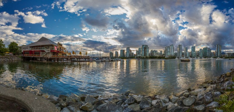 Vancouver, B.C. is reflected in the bay as dusk settles on the city.