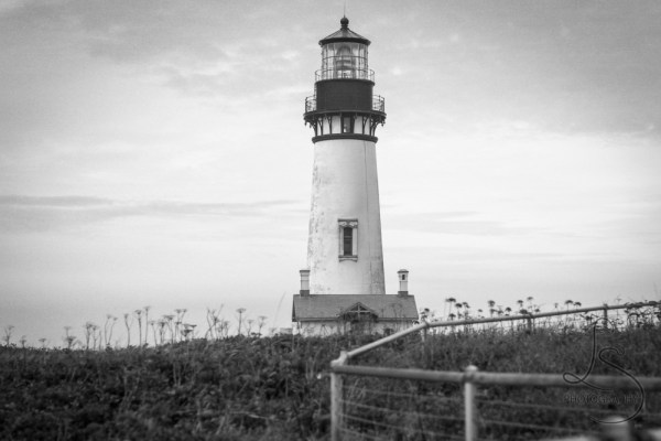 The Yaquina Lighthouse behind the zig zag line of a fence near Newport, Oregon   LotsaSmiles Photography