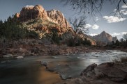 The sun sets on the river that rests in the shadow of Zion's Watchman