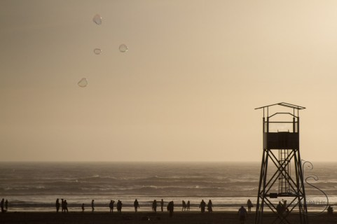 Giant bubbles float over the water at Seaside as beachgoers enjoy the evening sun.