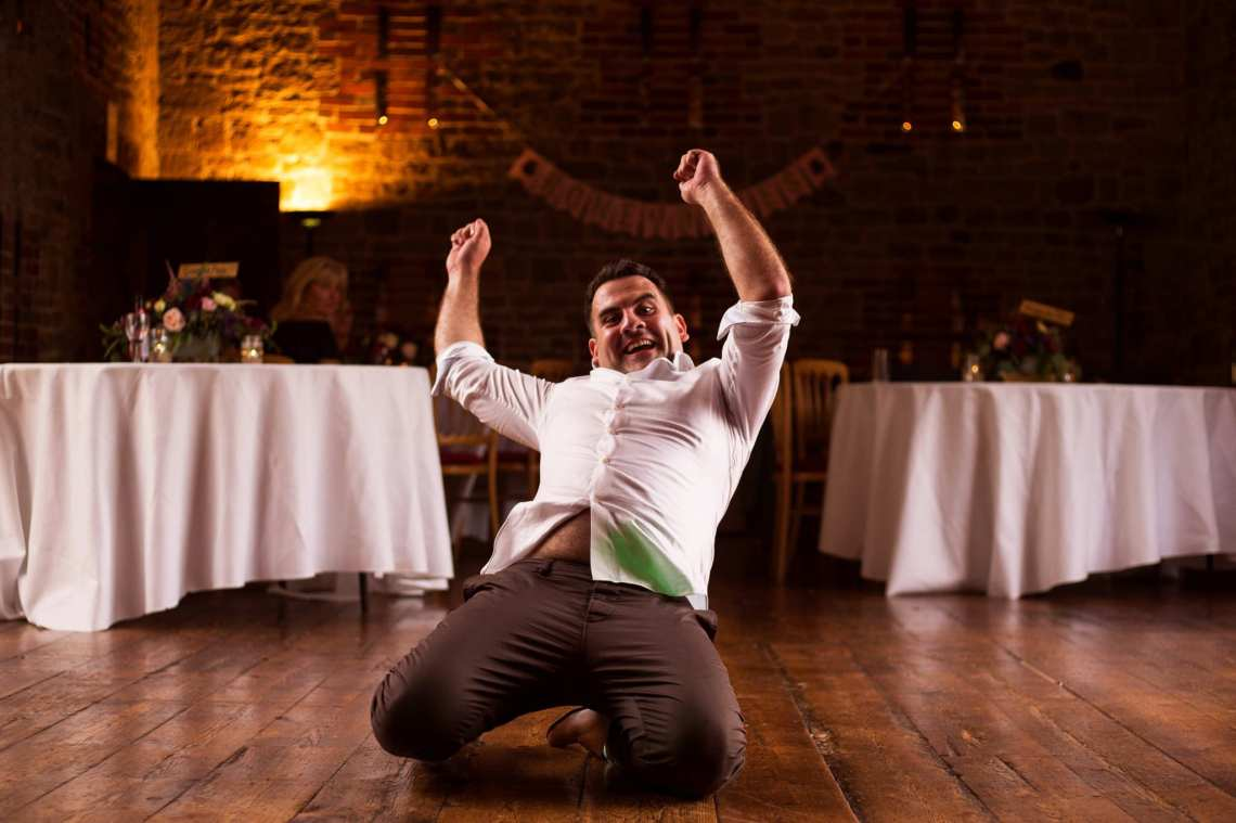 Wedding guest sliding on his knees in the middle of the dance floor by London wedding photographer, Lottie Povall
