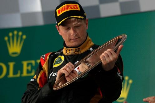 Kimi Raikkonen, Lotus F1, 1st position, celebrates on the podium with his trophy.