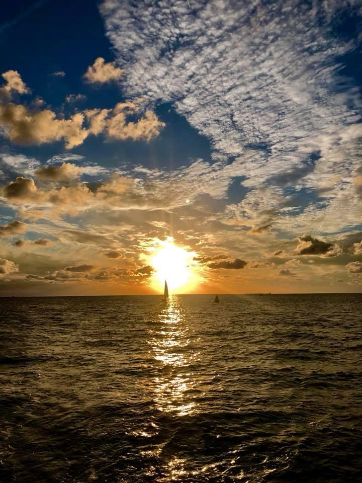 De zonsondergang tegemoet zeilen