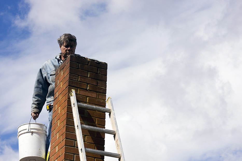 mason on a ladder repairing a damaged chimney