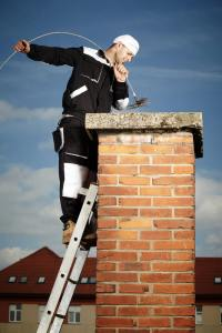 chimney sweep at the top of chimney with brush