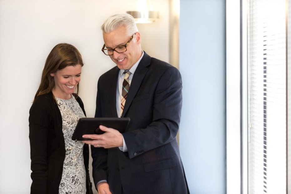 a businessman in a suit and a female executive sharing a tablet as photographed for a photography campaign by Loudbyte