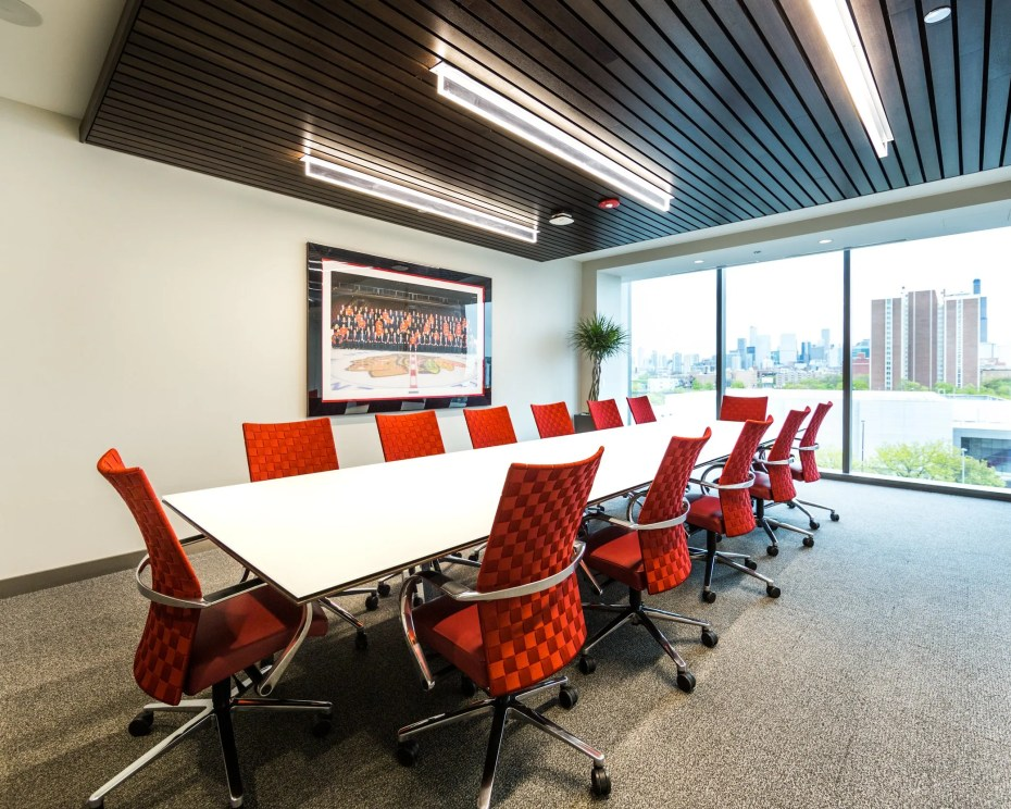 Empty board room with bright red chairs and a picture of united center on the wall photographed for a digital marketing campaign by Loudbyte