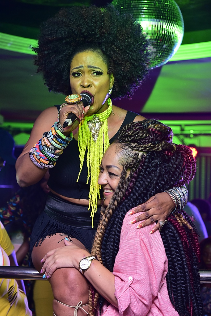1NITE LIVE & UNPLUGGED with MUMA GEE in performance mode in a sisterly hug with Elvina Ibru