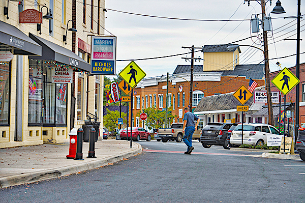 """A picture of a man crossing N. 21st Street in """"downtown"""" Purcellville."""