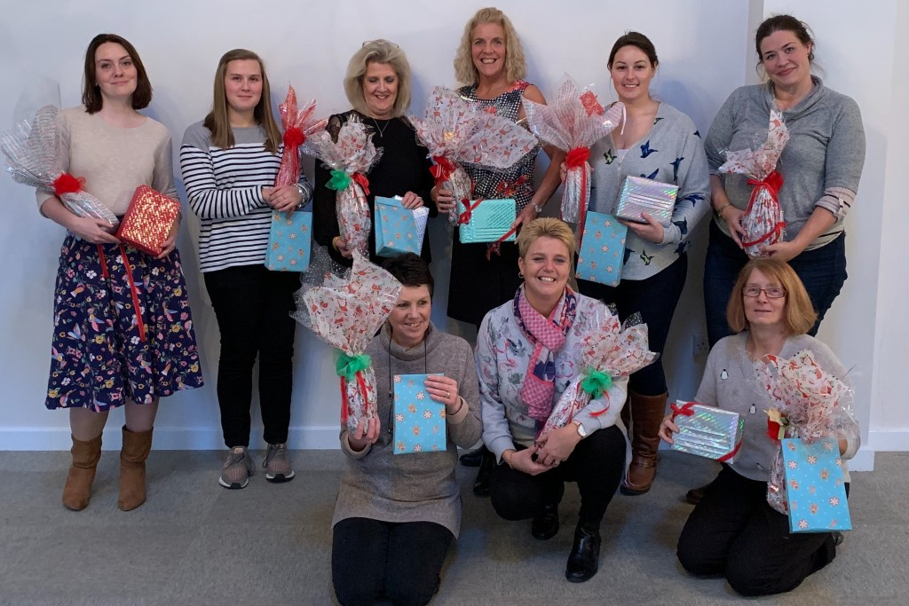 A group of ladies showing off their giftwrapping expertise, holding up creative bottles wrapped, boxes and gift bags