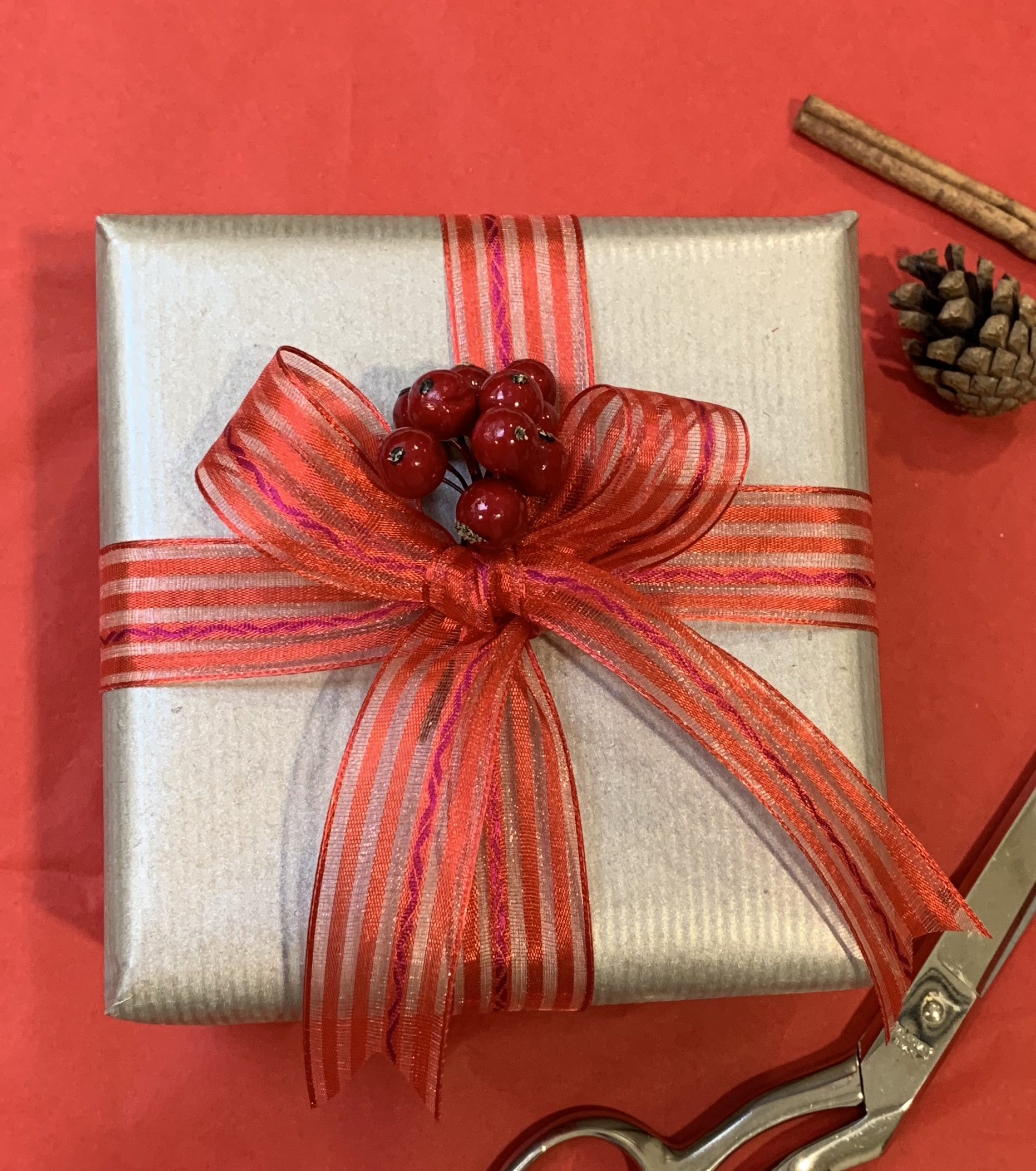 A box wrapped in silver paper with a red ribbon and bow