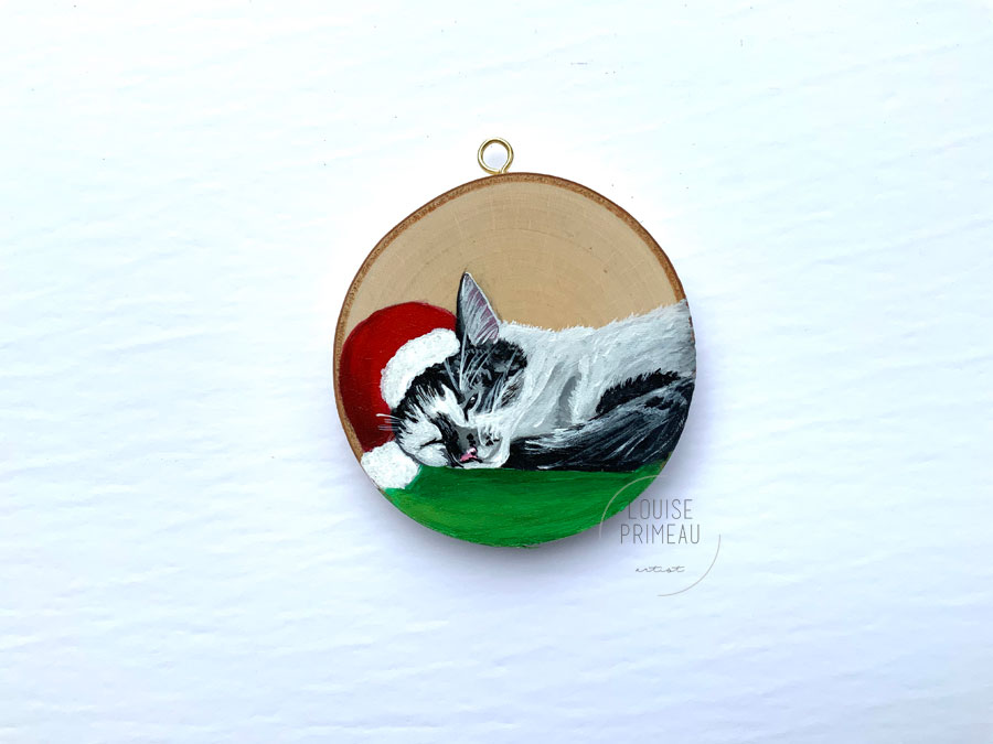 Wood slice ornament of Iggy, Christmas feline, sleeping.