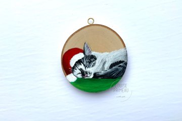 Wood slice ornament of Iggy, Christmas feline, sleeping.