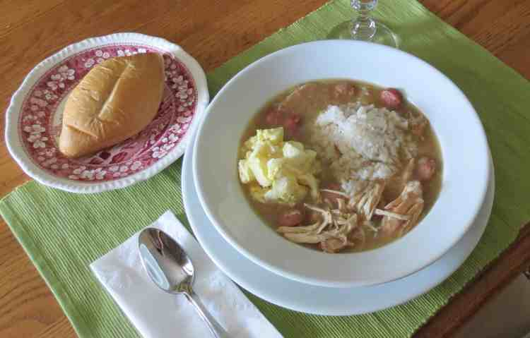 A white bowl of gumbo on a green place mat with a roll on a red and white plate.