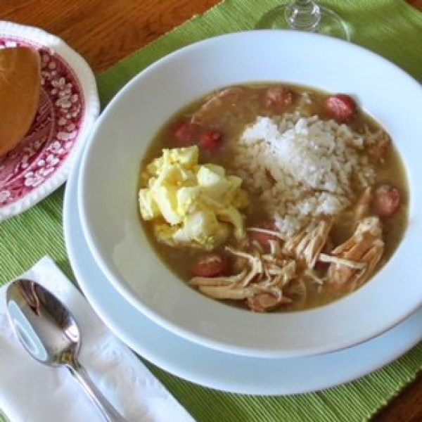 Bowl of Chicken Gumbo with a scoop of rice and potato salad in it