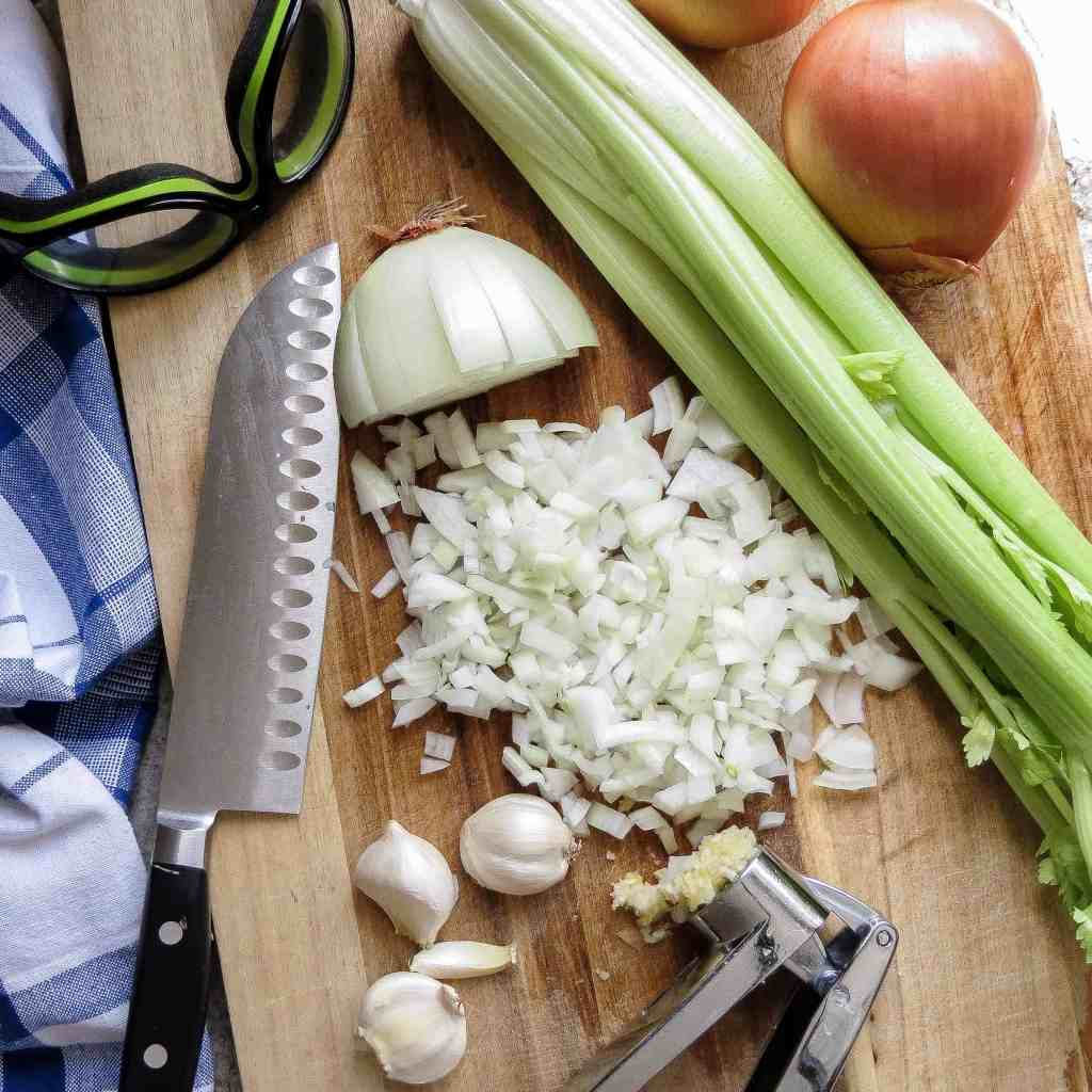 Onions, celery, garlic, and knife on wooden cutting board for Chicken Gumbo, Simply Classic Cajun.