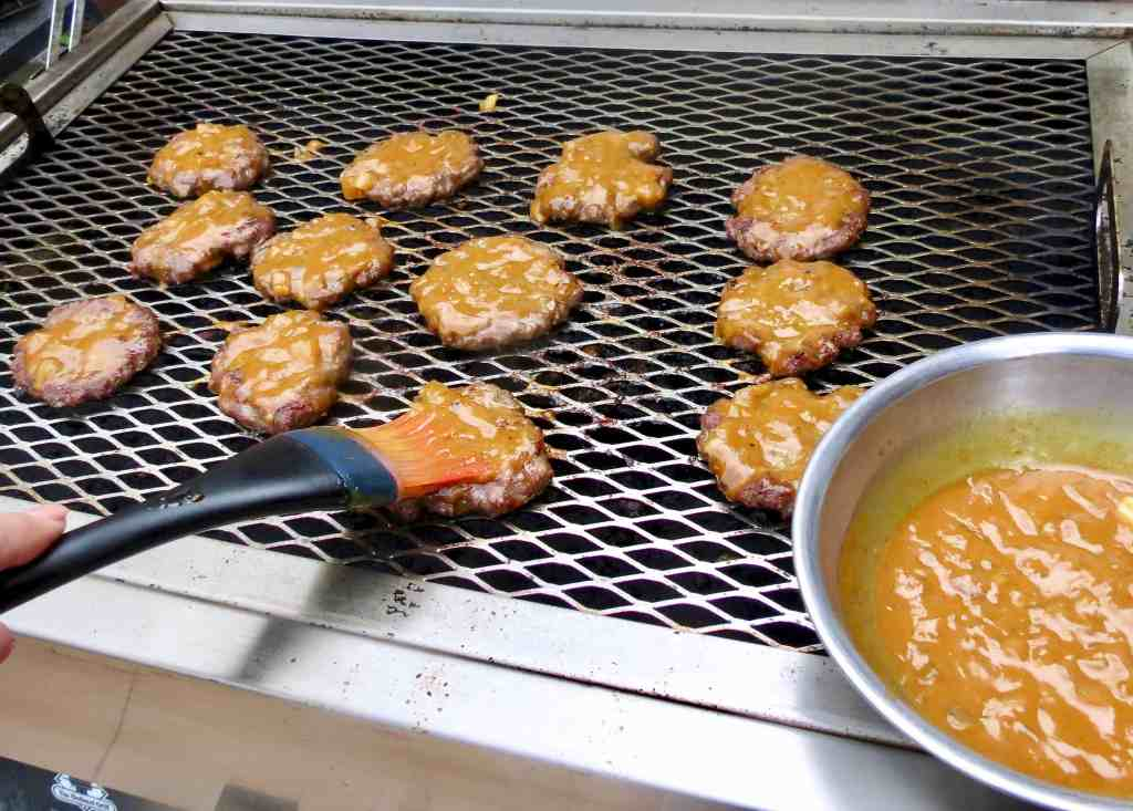 Burgers on the grill with a brush spreading mustard barbecue sauce on them.
