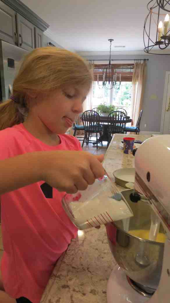 Little girl pouring buttermilk into a mixing bowl.