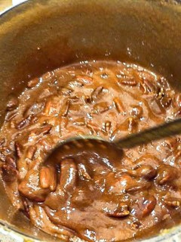 A spoon stirring pecans in pralines.