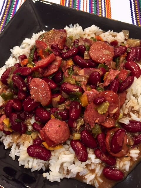 """A plateful of white rice topped with """"Va Vite"""" Red Beans And Rice."""